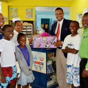 Carlong Donates Books to Pediatric Unit at the Savanna-La-Mar Hospital - Vinton Samms, Marketing Manager, and Nicklaus Bromfield, Marketing Representative, gift books to the Book Industry Association of Jamaica (BIAJ) book cart.