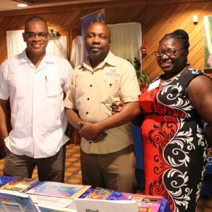 Carlong Booksellers' Seminar Mobay 2018 - Customer Service Administrator Delores Grant-Smith (right) and Marketing Reps Nicklaus Bromfield (left) and Domion Shorter (centre) manning Carlong's showcase of titles at the annual Booksellers' Seminar at the Pe