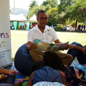 KBF Book Fair 2018 - Carlong Marketing Rep Nicklaus reads to children inside Do Good JA's Crayons Count tent at the Kingston Book Festival Book Fair in March 2018.